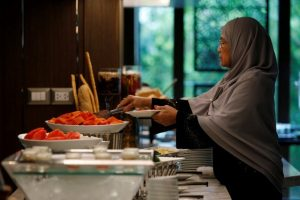 A Muslim visitor takes food from a platter for her breakfast at the Al Meroz hotel in Bangkok, Thailand, August 29, 2016. REUTERS/Chaiwat Subprasom