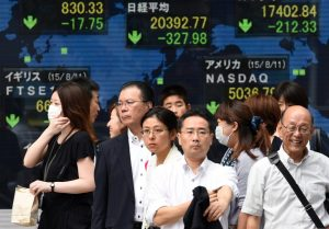 epa04880620 Pedestrians stand before a markets indicator board in Tokyo, Japan, 12 August 2015. Tokyo stocks dropped after China's central bank devalued the yuan for the second time in two days, to aid a slowing economy. The Nikkei Stock Average lost 327.98 points, or 1.58 per cent, to close at 20,392.77. EPA/FRANCK ROBICHON +++(c) dpa - Bildfunk+++