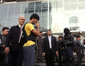 epa04921354 An Erawan Shrine bombing suspect, identified by Thai police as Yusufu Mieraili (C-L) who was arrested holding a Chinese passport, during a crime reenactment outside a shopping center opposite of the Erawan Shrine in Bangkok, Thailand, 09 September 2015. Yusufu was arrested by Thai police on the Thai-Cambodian border in connection with the Erawan Shrine bombing in Bangkok and  confessed to owning bomb-making materials found in an apartment in Bangkok. The bombing at the Hindu Shrine killed at least 20 people and injured more than a hundred.  EPA/RUNGROJ YONGRIT
