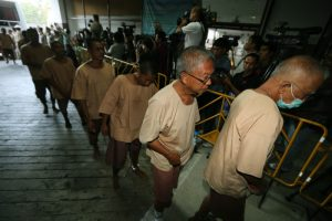 epa05018602 Suspects, allegedly involved in human trafficking of Rohingya migrants, are escorted by prison officials as they arrive at a criminal court in Bangkok, Thailand, 10 November 2015. Some 88 people allegedly involved in human trafficking of Rohingya migrants were summoned to court for the examination of evidence in the case, as according to authorities police officers, soldiers and local politicians in southern Thailand profited off the exodus of Rohingya Muslim migrants from Myanmar and Bangladesh. More than 150 warrants have been issued against officials suspected of their involvement in the trafficking ring, with 88 detained including a general. The trafficking network came to light earlier this year after investigators discovered mass graves of refugees at a trafficking camp in southern Thailand.  EPA/NARONG SANGNAK