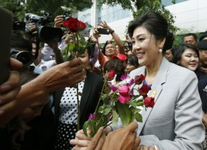 epa05001309 Former Thai prime minister Yingluck Shinawatra (R) receives flowers from supporters after appearing at a trial on criminal charges stemming from her government's rice price subsidy, at the Supreme Court's Criminal Division for Holders of Political Positions, in Bangkok, Thailand, 29 October 2015. The rice subsidy plan was a key promise during Yingluck Shinawatra's Pheu Thai party's 2011 electoral campaign. It was also a major talking point for her opposition which accused the government of mismanagement and corruption related to the scheme. Under the plan, the government bought rice from farmers at a fixed rate, sometimes 50 per cent higher than world market prices. Fluctuations in market prices and mismanagement of the stockpiles led to large losses. A military-appointed legislature and the lower courts have already impeached Yingluck over the scheme, resulting in a five-year ban from politics.  EPA/NARONG SANGNAK