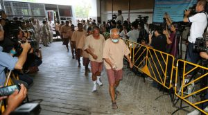 epa05018597 Suspects, allegedly involved in human trafficking of Rohingya migrants, are escorted by prison officials as they arrive at a criminal court in Bangkok, Thailand, 10 November 2015. Some 88 people allegedly involved in human trafficking of Rohingya migrants were summoned to court for the examination of evidence in the case, as according to authorities police officers, soldiers and local politicians in southern Thailand profited off the exodus of Rohingya Muslim migrants from Myanmar and Bangladesh. More than 150 warrants have been issued against officials suspected of their involvement in the trafficking ring, with 88 detained including a general. The trafficking network came to light earlier this year after investigators discovered mass graves of refugees at a trafficking camp in southern Thailand.  EPA/NARONG SANGNAK