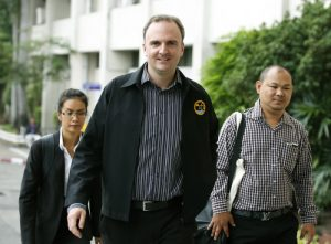 epa05099353 British lawyer and migrant workers' rights activist, Andy Hall (C) arrives at the Bangkok South Criminal Court in Bangkok, Thailand, 13 January 2016. Hall has been charged over computer crimes and criminal defamation in a case filed by Thai pineapple company, the Natural Fruit Company. The Natural Fruit in early 2013 filed four cases against Hall including two criminal defamation charges, a criminal charge under the Computer Crimes Act, and two civil defamation actions, after the publication and dissemination of the Finnwatch report 'Cheap Has a High Price'.  EPA/NARONG SANGNAK