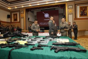 epa04999671 Thai national police chief Chakthip Chaijinda (R) inspects confiscated guns and other valuables seized from people allegedly involved in a network involved with a lese majeste case during a press conference at Royal Thai Police headquarters in Bangkok, Thailand, 28 October 2015. According to media reports, at least three people believed to be involved in a network seeking personal benefits from people by claiming connections with the monarchy have been arrested.  EPA/RUNGROJ YONGRIT